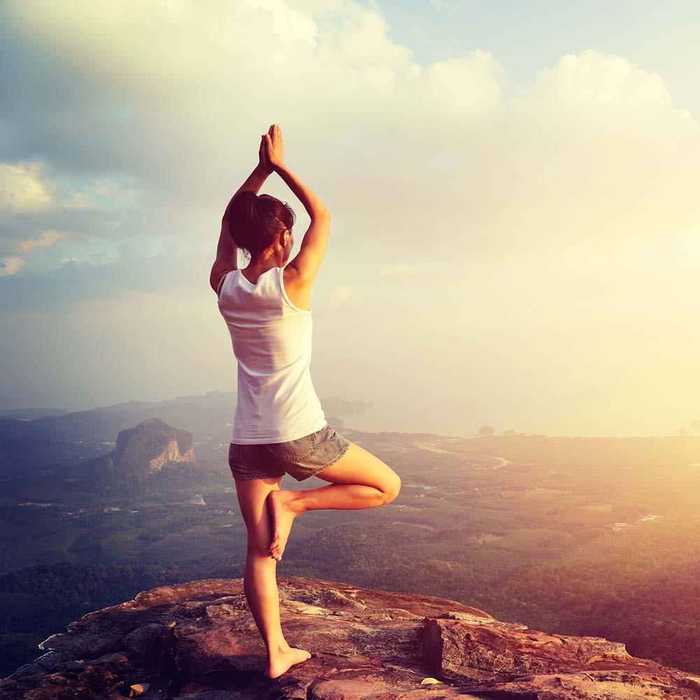 frau steht auf berg yoga